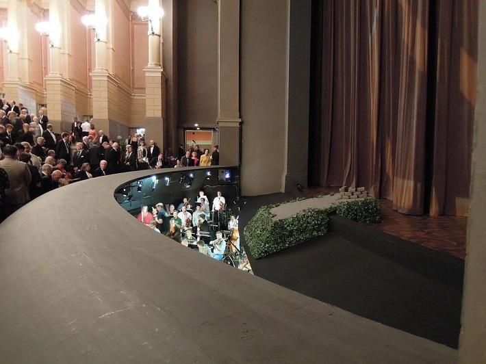 účinkujúci vidia hráčov orchestra len na najvyšších schodoch, diváci nevidia hráčov vôbec