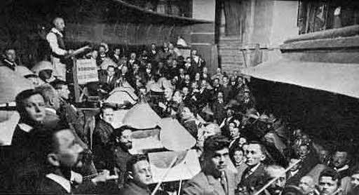 na dobových snímkach sedia hráči orchestra oproti sebe