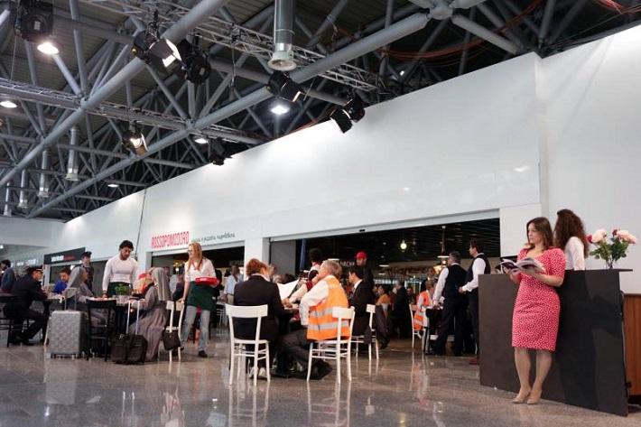 Donizetti na letisku Malpensa, úplne vpravo opretá o pult Eleonora Buratto (Adina)