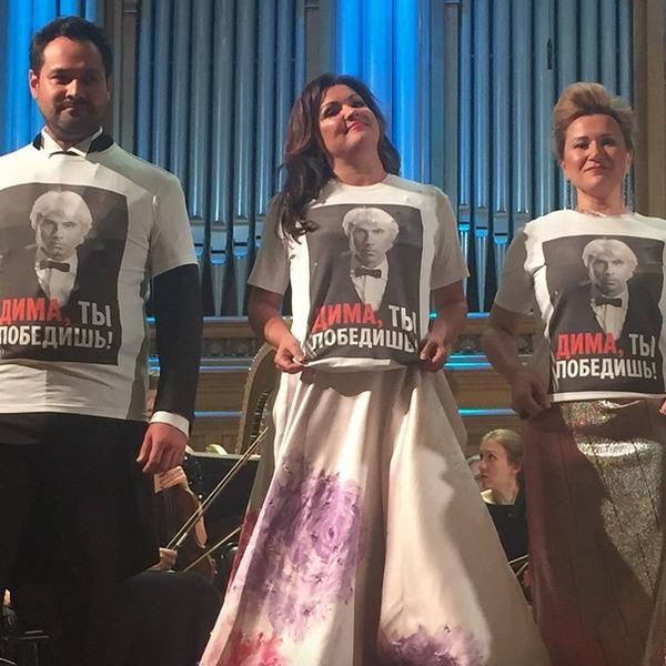 """I. Abdrazakov, A. Netrebko a J. Gubanova s nápisom ,,Dima, ty zvíťazíš!"""" vyjadrili podporu chorému kolegovi počas svojho koncertu 8. júla 2015 v Moskve., foto: Twitter"""